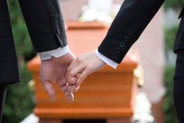 People holding hands at the funeral of a wrongful death victim in Virginia.