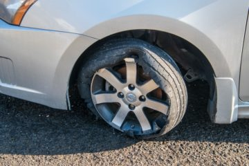 Car tire that has a blowout with rim and car damage.