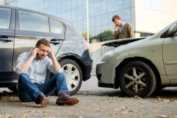Two men involved in car accident calling their respective insurance company.